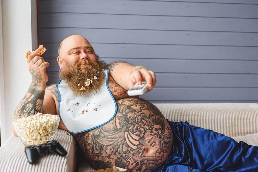 Homem gordo assistindo televisão