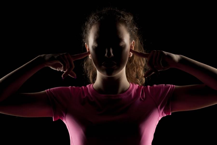 Mulher tampando seus ouvidos na sala do silêncio.