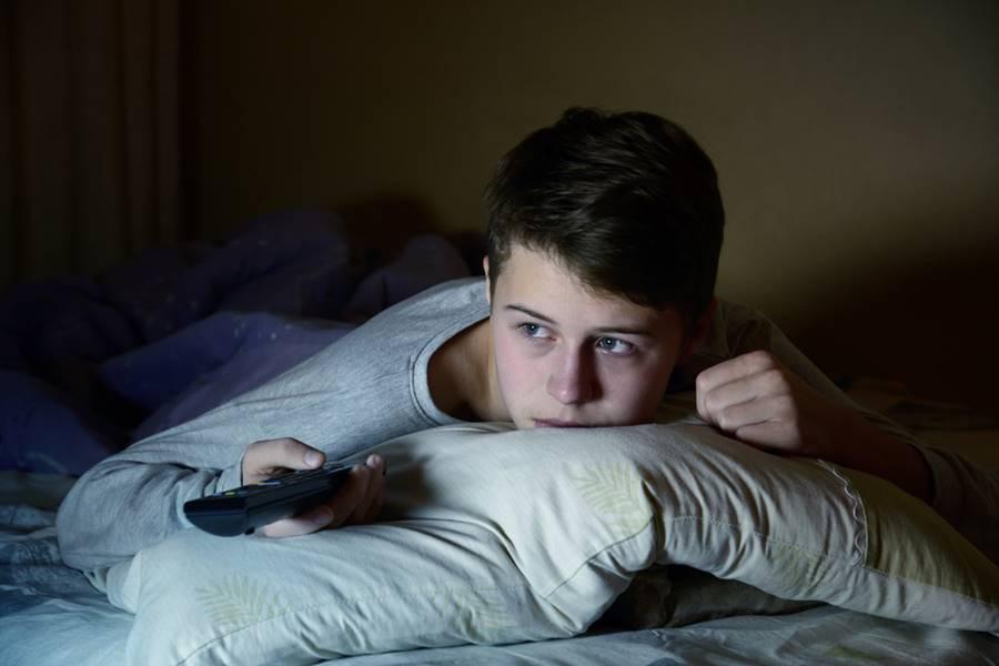 Menino deitado na cama assistindo à séries